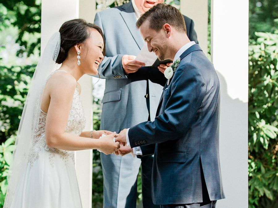 Bride and groom laughing while exchanging rings - Elegant/Spring/June/Blush/Blue/Peach